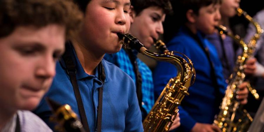 From left, Richmond Middle School students James Hackett, Eric Chen, Luke Holmes, Aaron Matthew and Nina Sablan practice before playing in a band concert at Hanover High School in Hanover, N.H., on April 4, 2018. The Richmond Middle School Jazz Band opened the concert, playing four songs. (Valley News - Carly Geraci) Copyright Valley News. May not be reprinted or used online without permission. Send requests to permission@vnews.com.